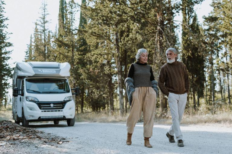 coppia a passeggio in montagna con camper mobilvetta sullo sfondo